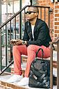USA, NYC, Brooklyn, Man waiting on stairs, using smartphone - JUBF00224