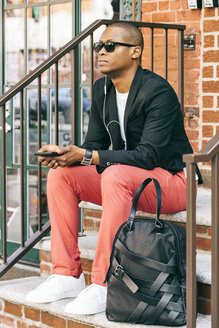 USA, NYC, Brooklyn, Man waiting on stairs, using smartphone - JUBF00224