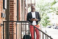 USA, NYC, Brooklyn, Man waiting on stairs, using smartphone - JUBF00227