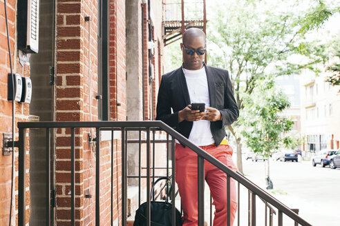 USA, NYC, Brooklyn, Man waiting on stairs, using smartphone - JUBF00227