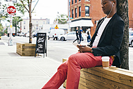 Man sitting in the street, using digital tablet, drinking coffee - JUBF00230