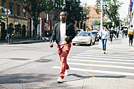 USA, NYC, Brooklyn, Man walking in the street, holding cup of coffee - JUBF00236