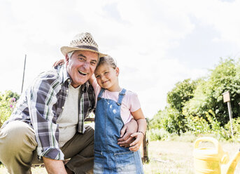 Portrait of happy grandfather and granddaughter in the garden - UUF11336