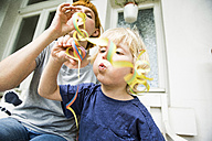 Toddler with mother on balcony blowing streamer - SPFF00003