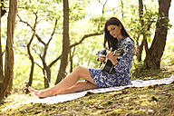 Young woman playing guitar in forest - MFRF00936