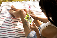 Young woman sitting on blanket looking at instant photo - MFRF00945