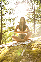 Young woman sitting on blanket in forest practicing yoga - MFRF00948