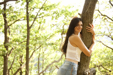 Young woman in forest hugging a tree - MFRF00951