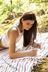 Young woman lying on blanket in forest writing a letter - MFRF00954