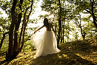 Rear view of young woman in forest wearing tulle skirt - MFRF00960