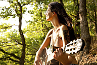 Young woman playing guitar in forest - MFRF00963