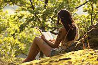 Young woman in forest holding flowers reading a book - MFRF00966