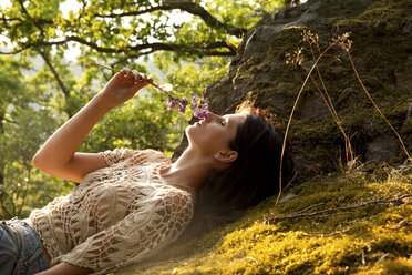 Young woman lying in forest smelling at bunch of flowers - MFRF00969