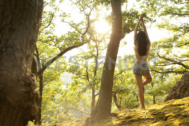 Young woman in forest practicing yoga - MFRF00972