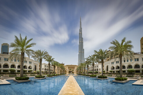 United Arab Emirates, Dubai, Burj Khalifa with traditional styled houses around a water basin with palm trees - NKF00482