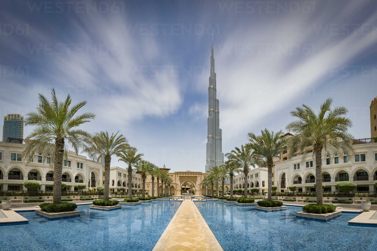 United Arab Emirates, Dubai, Burj Khalifa with traditional styled houses around a water basin with palm trees - NKF00482 - Stefan Kunert/Westend61