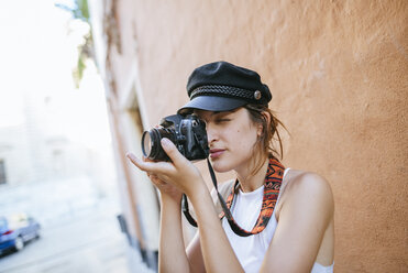 Young woman with hat taking a photo with a camera - KIJF01671