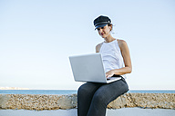 Young woman with hat using a laptop outdoors - KIJF01677