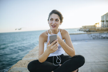 Young woman talking with hands-free phone on boardwalk - KIJF01680