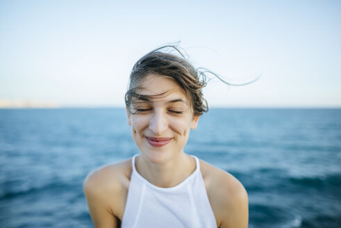 Young woman smiling with eyes closed with sea background - KIJF01683