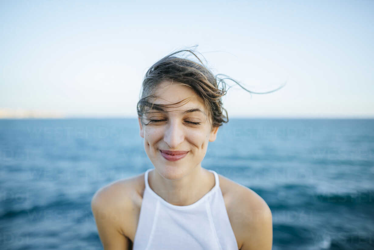 Young woman smiling with eyes closed with sea background - KIJF01683 - Kiko Jimenez/Westend61
