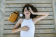 Young woman lying on wooden path next to ball and baseball glove - KIJF01692