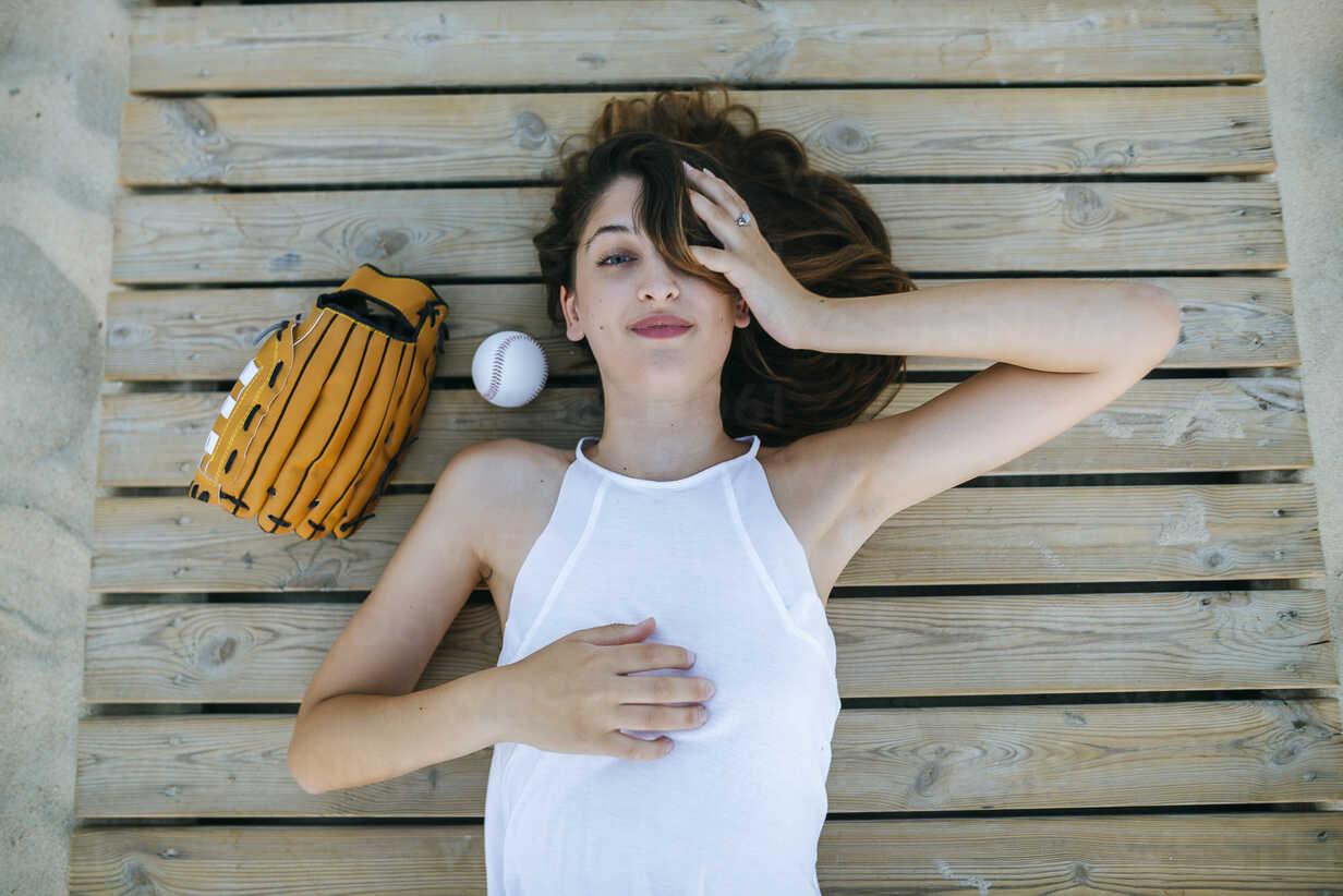 Young woman lying on wooden path next to ball and baseball glove - KIJF01692 - Kiko Jimenez/Westend61