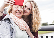Grandmother and granddaughter taking selfie with smartphone - UUF11351