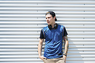 Tattooed young man with headphones and hands in pockets - FMOF00285