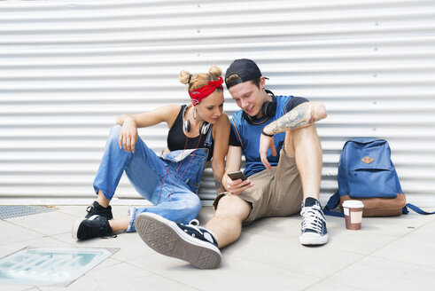 Young couple sitting on ground looking at smartphone - FMOF00294