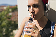 Portrait of young woman with headphones drinking soft drink - FMOF00312