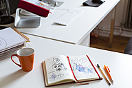 Notebook with sketch and cup of coffee on desk in office - FKF02451