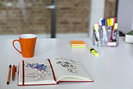 Notebook with sketch and cup of coffee on desk in office - FKF02454