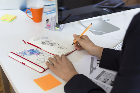 Woman drawing into notebook at desk in office - FKF02457