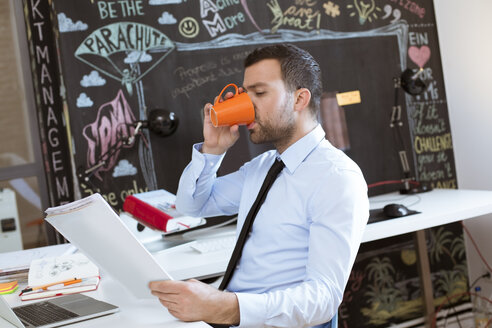 Businessman in creative office looking at documents and drinking coffee - FKF02469