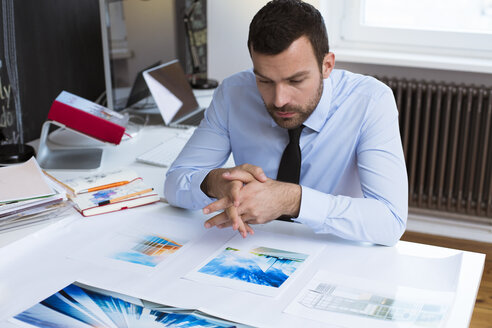 Businessman at desk in office looking at printouts - FKF02472