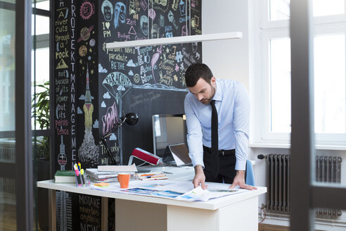 Businessman at desk in office looking at printouts - FKF02475