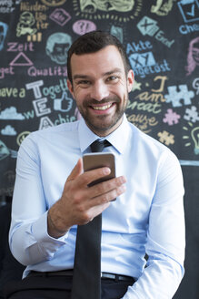 Portrait of smiling businessman with cell phone in creative office - FKF02478