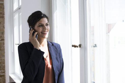Smiling businesswoman on the phone at the window - FKF02499