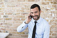 Portrait of smiling businessman on the phone at brick wall - FKF02508