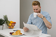 Businessman drinking coffee while reading newspaper in the morning at home - MOMF00196