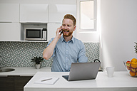Businessman with laptop talking on the phone in his kitchen - MOMF00199