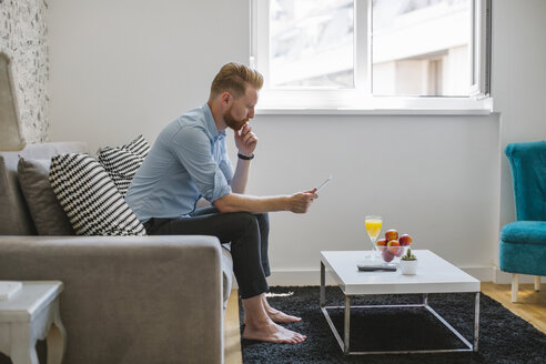 Businessman sitting on couch at his living room looking at smartphone - MOMF00202