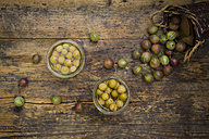 Two jars of preserved gooseberries and gooseberries on wood - LVF06264