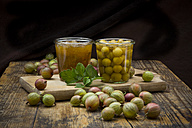 Jar of gooseberry jam, gooseberries and glass of preserved gooseberries on wood - LVF06270