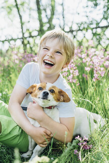 Portrait of laughing little boy sitting with his dog on meadow in the garden - MJF02133