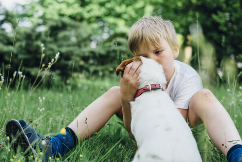 Little boy sitting with his dog on meadow in the garden - MJF02136