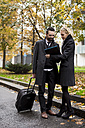Businessman and businesswoman in the city looking at folder - MAUF01180