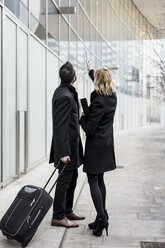 Businessman and businesswoman in the city looking at building - MAUF01186