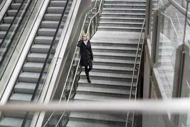 Businesswoman on stairs with cell phone - MAUF01198